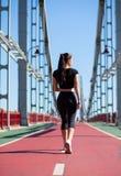 Habillement de port de sport de jolie femme de forme physique marchant au pont photographie stock