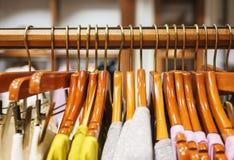 Habillement du ` s de femmes à la mode sur les cintres en bois dans un magasin d'habillement moderne images stock