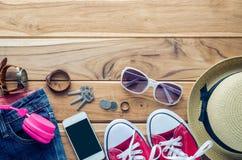 Habillement et accessoires pour le voyage sur le plancher en bois Photos stock