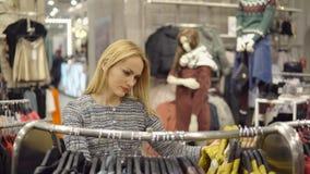 Habillement, garde-robe, mode, style et concept de personnes - femme blonde heureuse choisissant l'habillement dans le magasin Images stock