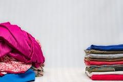Habillement plié à côté de la pile des vêtements dévoilés Images libres de droits
