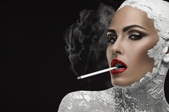 Habit and aftermath. Beautiful and well-groomed woman smoking a cigarette, a habit royalty free stock photography