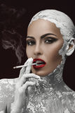 Habit and aftermath. Beautiful and well-groomed woman smoking a cigarette, a habit stock image