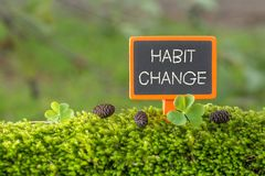 Habit change text on small blackboard. Sign on green moss with Clover , blur green tree plant background stock photography