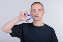 Habit. I quit smoking! Cheerful young man holding scissors near the cigarette while standing isolated on white background stock photography