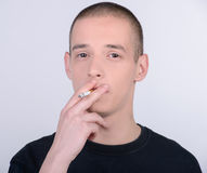 Habit. A young man smokes a cigarette on a gray background stock images