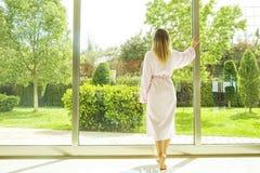 Habitación por completo de los haces del sol de la luz del sol Comienzo optimista Mujer rubia, ropa casera acogedora, luz del día imagenes de archivo
