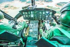 Habitacle militaire d'hélicoptère avec deux pilotes volant au-dessus d'un lac tropical images stock