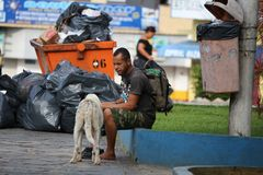 Habitant de rue du Brésil assis à côté des sacs de poubelle et de déchets Images stock