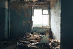 Habitation of homeless man inside in abandoned house. Peeling walls. Trash on the floor, window stock photo