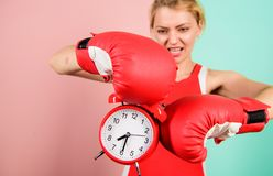 Habits and regime concept. Improve yourself. Overcome harmful habits. Time for training. Get used to personal regime. Girl athlete boxing gloves and alarm royalty free stock photos