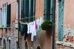Daily habits in Venice. Red brick historical buildings with clothes outside the green windows, habits in Venice, in Italy, Europe Stock Photography