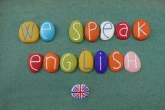 Hablamos inglés, consejo creativo compuesto con las letras coloreadas multi sobre la arena verde ilustración del vector