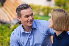 Hablar exterior de los pares felices y mirada de uno a Fotos de archivo