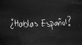 Hablas espanol?. Hablas espanol written on a blackboard Stock Images