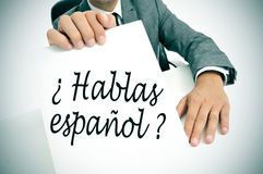 Hablas espanol? do you speak spanish? written in spanish. A man wearing a suit holding a signboard with the sentence hablas espanol? do you speak spanish? Royalty Free Stock Image