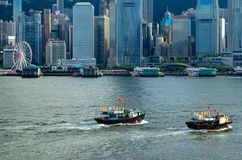 HABOUR城市香港,2019年6月08日:有航行在洪前面美好的地平线的中国和香港旗子的地方轮渡  免版税库存图片