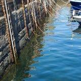 Habourmuur met kabelskettingen en ladders voor boten Stock Afbeelding