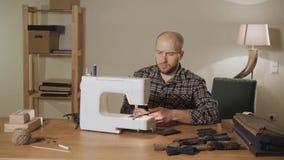 hace las corbatas de lazo Funcionamiento del hombre joven como sastre y usar una máquina de coser en un estudio de la materia tex almacen de video