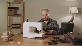 hace las corbatas de lazo Funcionamiento del hombre joven como sastre y usar una máquina de coser en un estudio de la materia tex metrajes