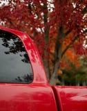 Hacer juego el color rojo del follaje del arce y de la camioneta pickup parqueada en R fotos de archivo