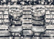 Hacer la cerveza a mano, dos tazas de cerveza en una tabla de madera en el pub Año Nuevo, la Navidad Vidrios de cerveza ligera en Imagenes de archivo