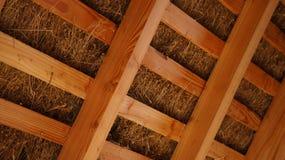 Haces de madera del viga del tejado cubierto con paja dentro Fotos de archivo libres de regalías