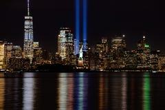 Haces de 9/11 monumento con la estatua de la libertad y del Lower Manhattan foto de archivo