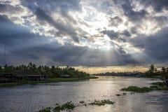Haces y cielo hermosos del sol sobre el riverMaenam Tha Chin, Nakhon Pathom, Tailandia de Tha Chin Imagen de archivo libre de regalías