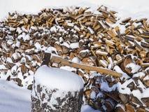 Hacha ascendente cercana atada al tronco del árbol en el fondo de la leña tajada llenada cubierta con nieve fotografía de archivo libre de regalías