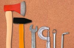 Hacha, martillo, destornillador y llaves sobre corcho Imagenes de archivo