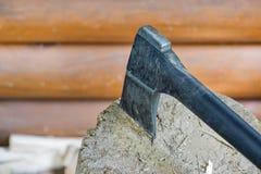 Hacha negra moderna en el registro y microprocesadores de madera después de cortar la leña para el invierno cerca de la casa de m Imágenes de archivo libres de regalías