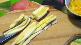 Hachage de banane Le cuisinier coupe des bananes sur le hachoir banque de vidéos
