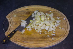 Hachage des oignons sur un hachoir en bois Photos libres de droits