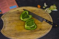 Hachage des poivrons verts sur un hachoir en bois photos libres de droits