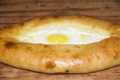 Hachapuri sulla torta aperta di Adjara con l'uovo su fondo di legno Immagine Stock