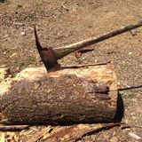 Hache logée dans le rondin après hachage du bois Image libre de droits