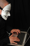 Hacher with computer. Member of the Anonymous hacker group in front of the laptop Royalty Free Stock Image
