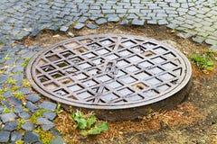 Hachez la couverture, drain de ville sur la route, système d'égouts de ville images stock