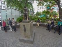 坐在长凳附近的日本人在Hachiko雕象 免版税库存照片