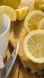 Hachoir en bois découpé et entier en tranches des citrons o une table Image libre de droits