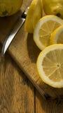 Hachoir en bois découpé et entier en tranches des citrons o une table Image stock