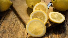 Hachoir en bois découpé et entier en tranches des citrons o une table Photographie stock