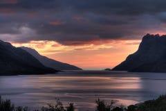 Hacia fuera al mar en la puesta del sol, puesta del sol del fiordo, Kvaløya, Noruega foto de archivo