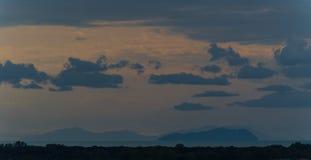Hacia fuera isla lejana de la puesta del sol con las nubes Fotos de archivo