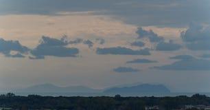 Hacia fuera isla lejana de la puesta del sol con las nubes Imagen de archivo libre de regalías