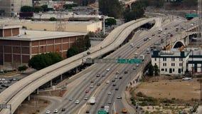 Hacia fuera/por encima del enfoque vista del tráfico en autopista sin peaje ocupada en Los Ángeles céntrico California almacen de video