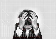 Hacia fuera subrayado hombre de negocios, con los gráficos de negocio hacia abajo El mercado de acción del fracaso y la inversión Imágenes de archivo libres de regalías