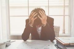 Hacia fuera subrayado un hombre de negocios lleva a cabo su cabeza en la desesperación Foto de archivo