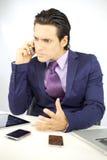 Hacia fuera tensionado hombre de negocios joven en el teléfono Imagen de archivo